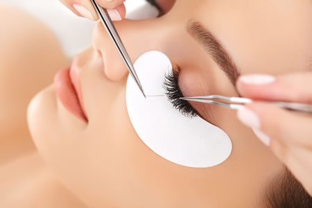 young woman having eye lash extensions applied